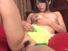 Naughty brunette asian chick plays with her pussy on the red couch